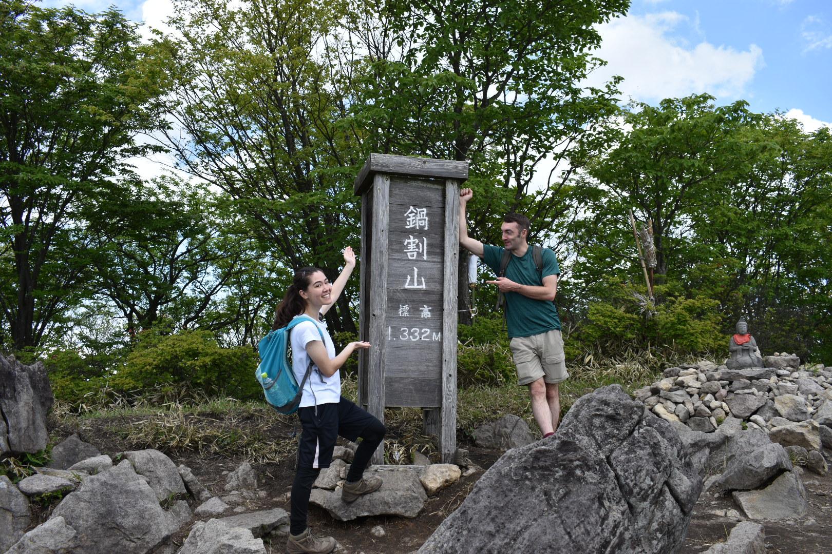 Two hikers at the Nabewariyama summit signpost