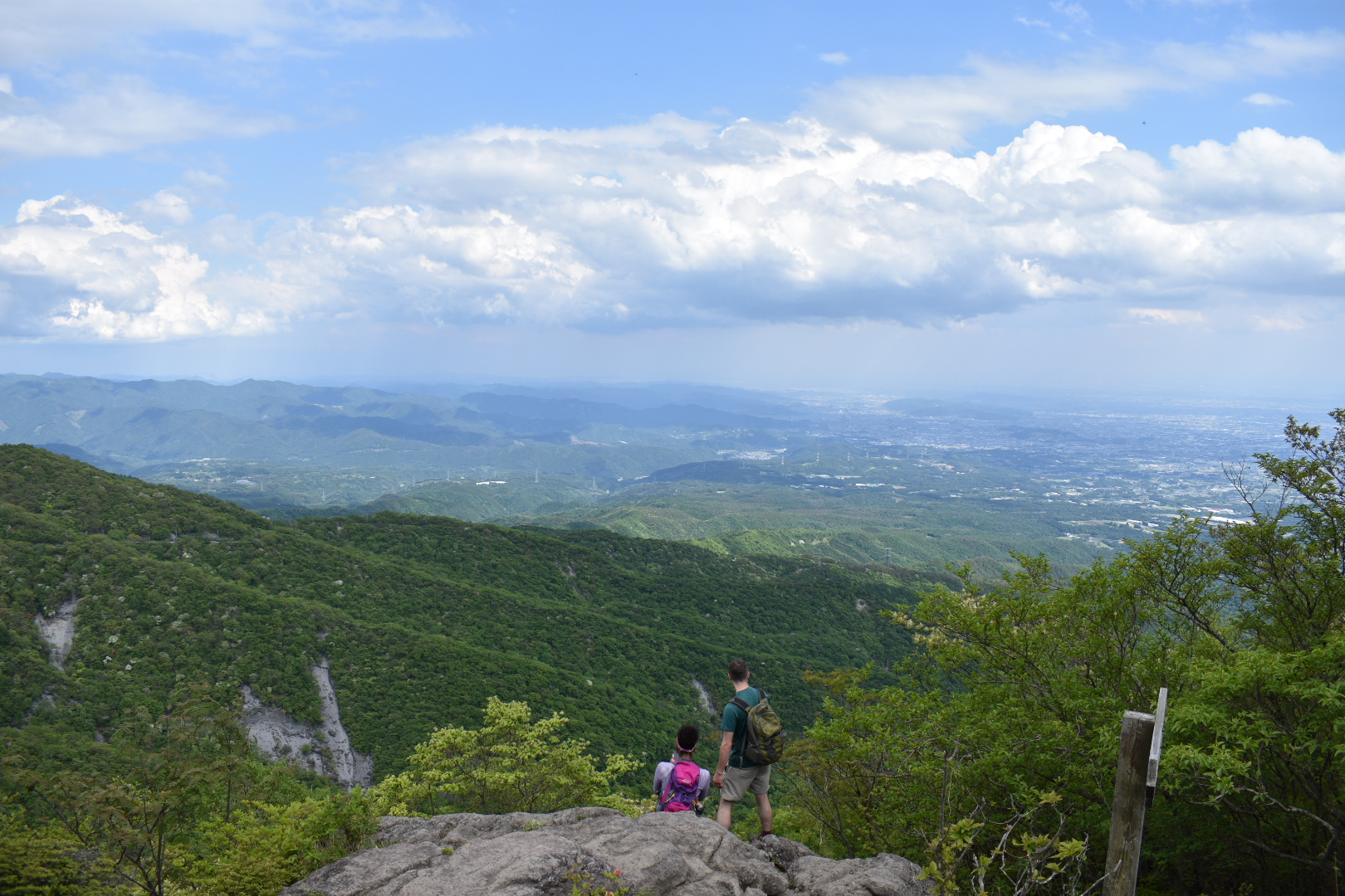 2 hikers looking out at a view of mountains and towns in the distance from Hisashi Iwa, Mt. Akagi