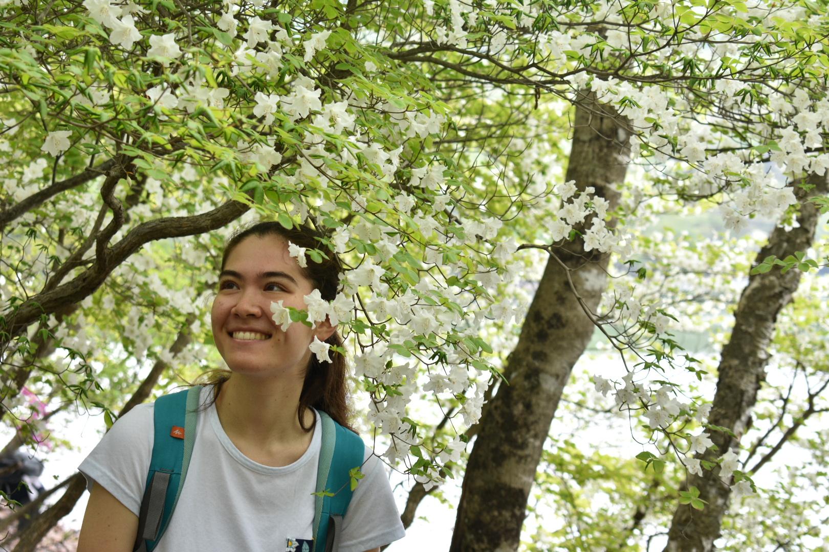 A hiker poses with white quinquefolium azaleas