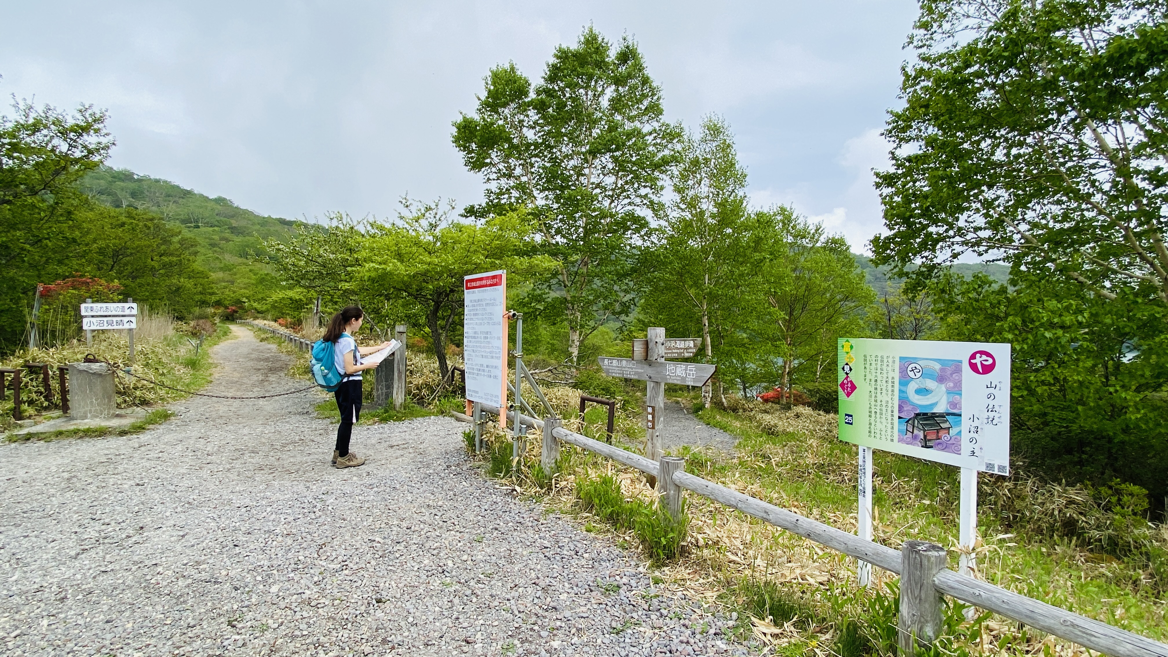 A hiker looks at a map next to two different trails