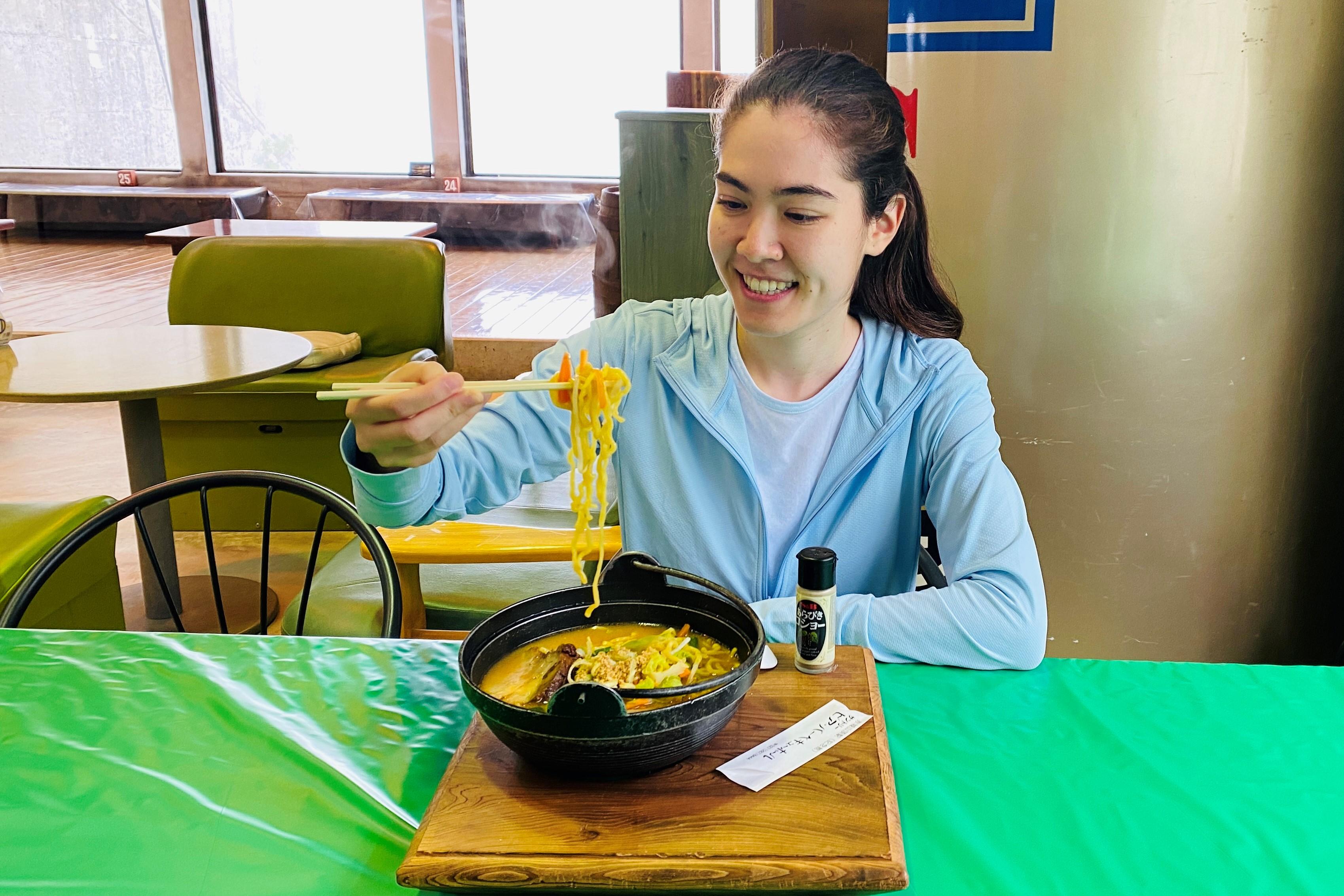 woman eating ramen noodle soup inside a restaurant